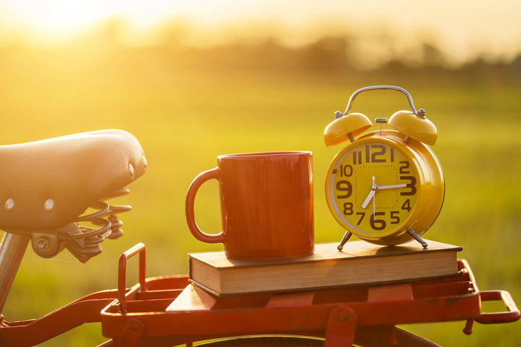 Close-up of clock on table at sunset