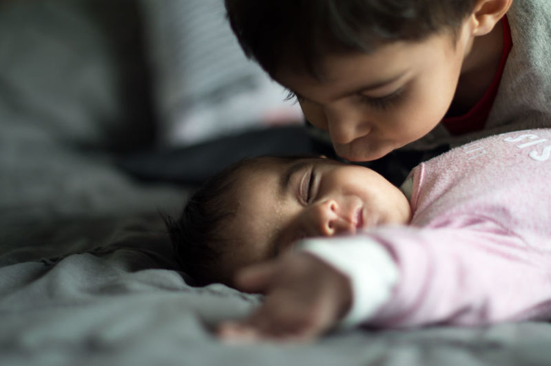 Older brother waking up a his sister baby with a sweet kiss
