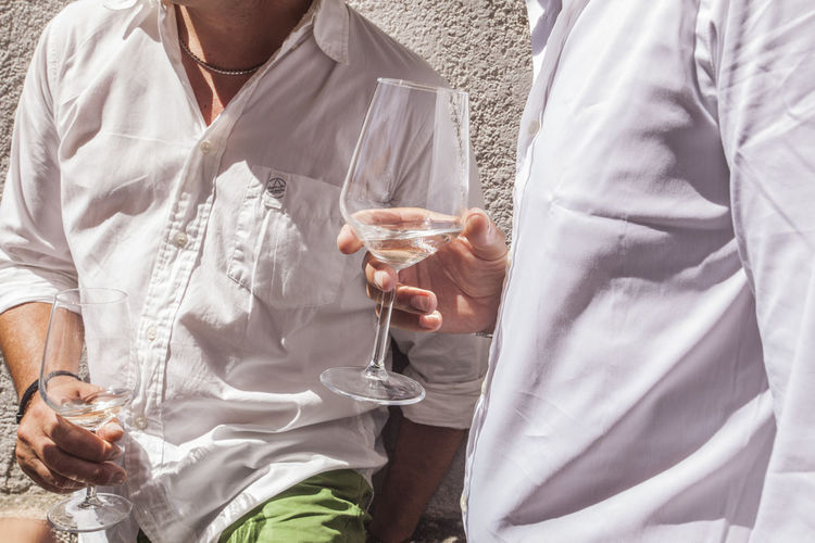 Midsection of friends drinking white wine during wedding