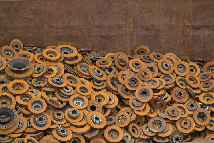 High angle view of rusty metallic wheels against wall