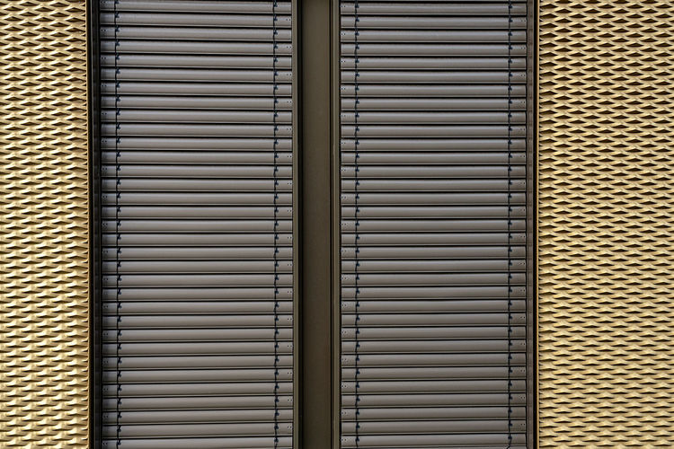 Golden background of sheet metal with pattern and brown blinds Golden Background Gold Full Frame Pattern Backgrounds No People Built Structure Blinds Textured  Repetition Indoors  Window In A Row Close-up Day Wall - Building Feature Closed Architecture Security Safety Shutter