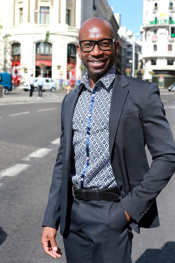Well-dressed smiling businessman in city