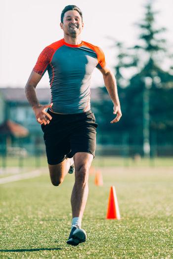 Full Length Of Man Running On Grassy Field