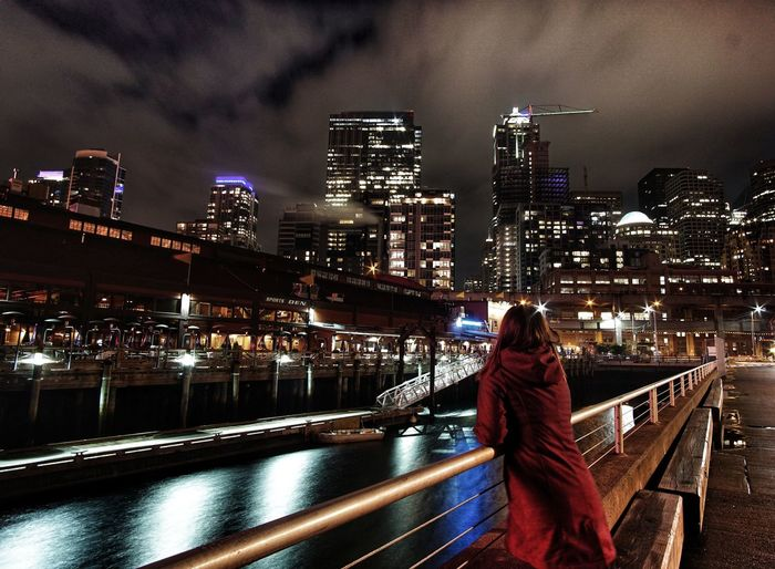 Rear view of woman standing on bridge by illuminated buildings in city at night
