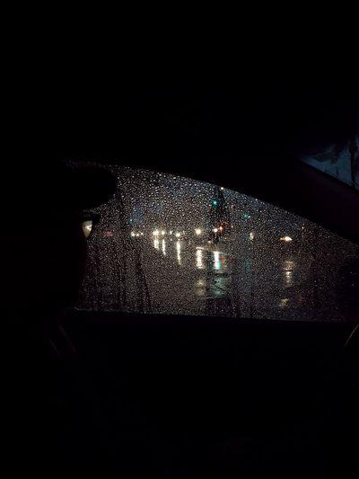 Illuminated city seen through wet glass