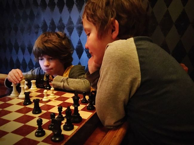 Chess Two People Chess Board Strategy Child Boys Childhood Chess Piece Playing Leisure Activity Concentration Competition Leisure Games Friendship Intelligence Togetherness Learning Family Skill  Indoors  Patterns Diamond Squares Colors Contratsts