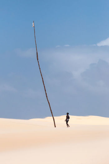 Man on sand dune in desert in front of a high rod against sky