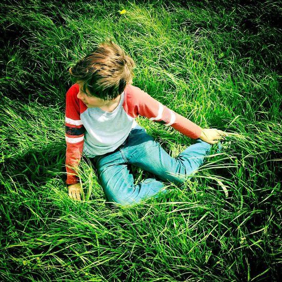 Full length of girl relaxing on grassy field