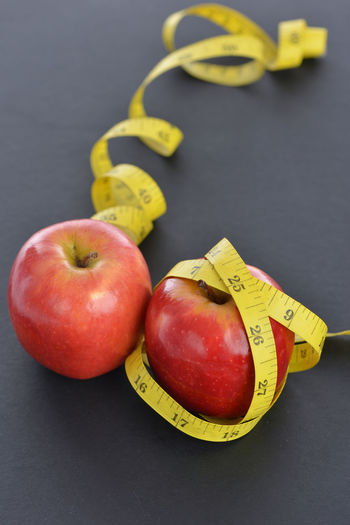 An apple with measuring rope Apple - Fruit Close-up Day Food Freshness Fruit Healthy Eating Healthy Lifestyle Indoors  Measuring Rope Measuring Tape No People Studio Shot Yellow
