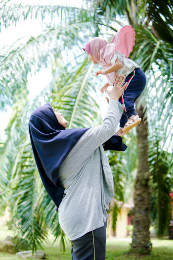 Side view of man holding woman standing against plants