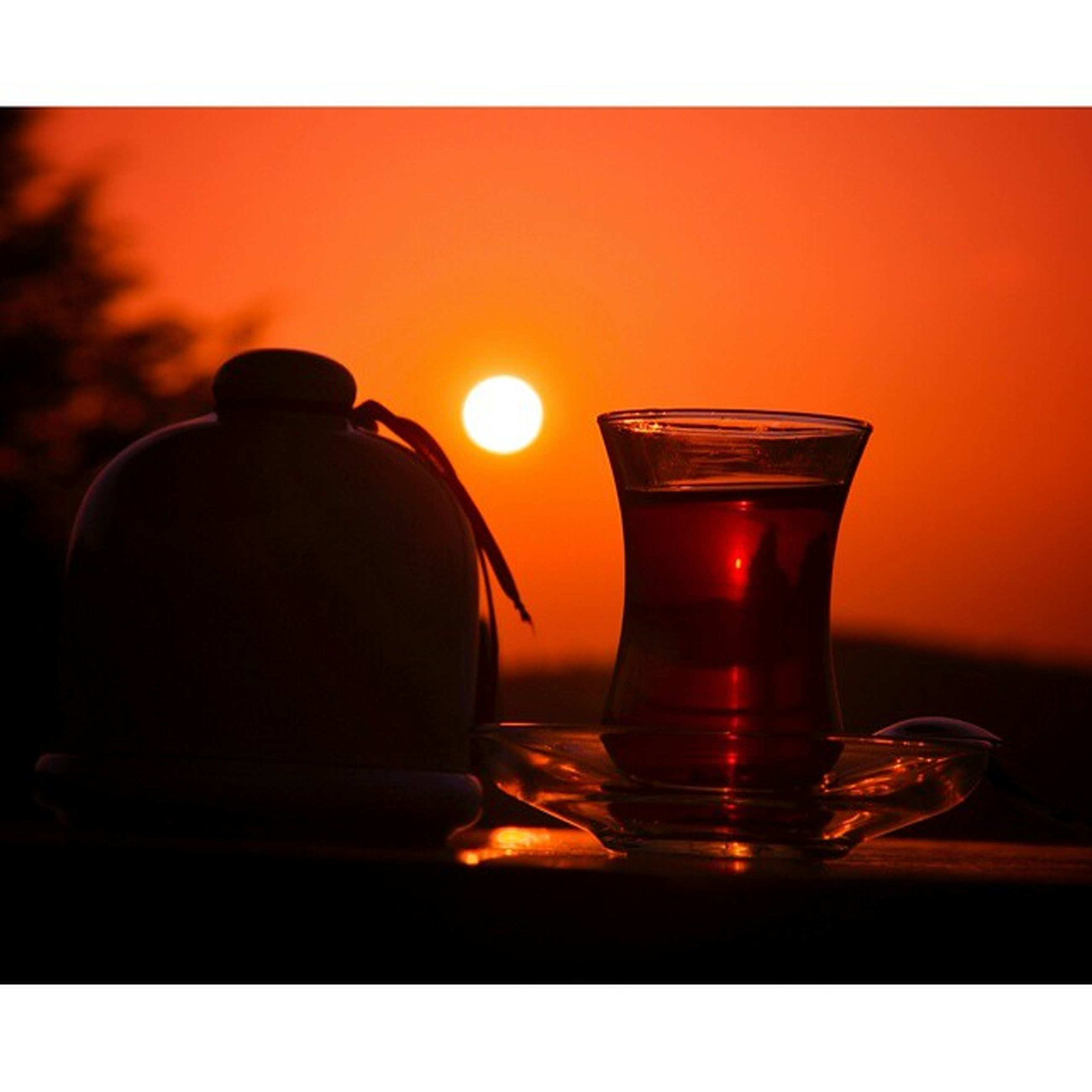 transfer print, auto post production filter, indoors, drink, glass - material, table, close-up, food and drink, drinking glass, transparent, refreshment, still life, sunset, orange color, glass, focus on foreground, freshness, no people, alcohol, reflection