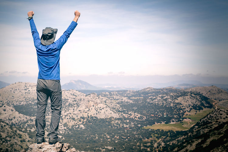 Rear View Of Man With Arms Raised Standing On Mountain