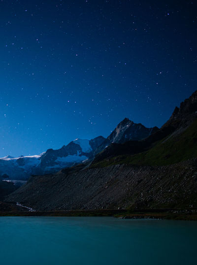 Scenic view of mountains against blue sky at night