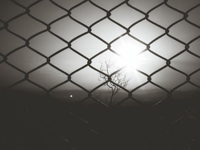 Landscape against sky seen through chainlink fence