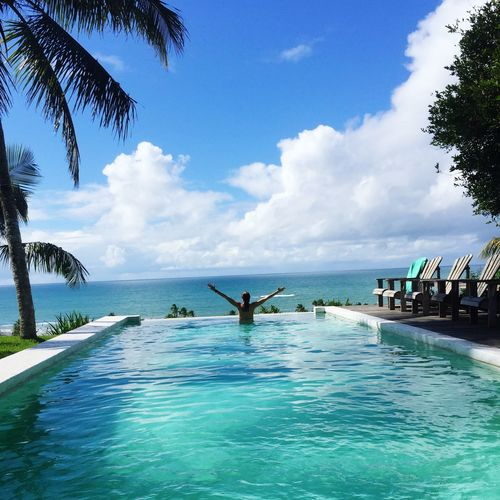 Rear view of woman with arms outstretched in infinity pool against sky