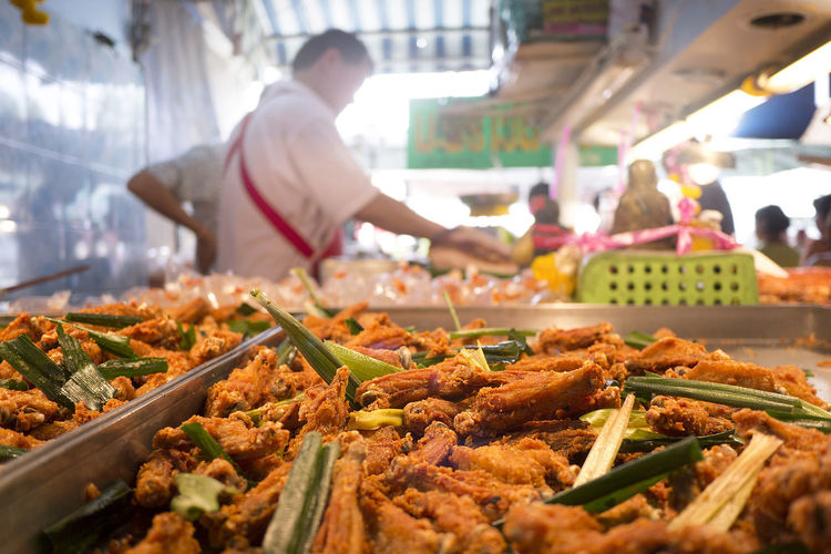 Close-up of fried chicken with lemon grass in tray for sale