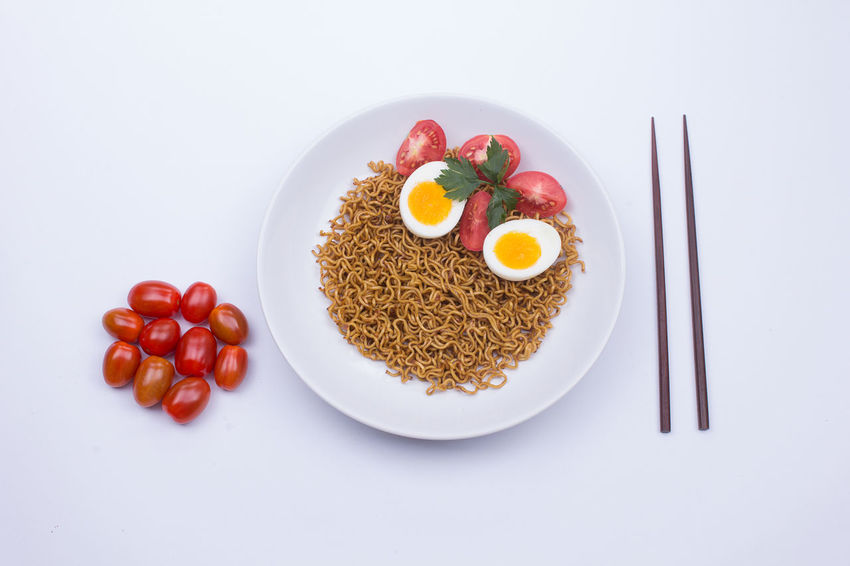 Fried noodle on a white plate styled beautifully Fried Noodles Noodles Breakfast Directly Above Egg Food Food And Drink Freshness Fruit Healthy Eating High Angle View Indoors  Meal No People Noodle Plate Ready-to-eat Still Life Studio Shot Tomato Vegetable Wellbeing White Background