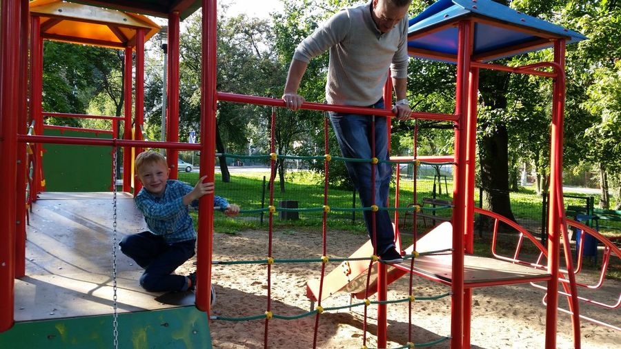 Full length of playful father and son at playground