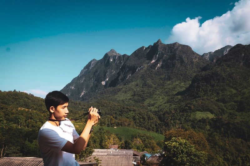 Side view of man photographing on mountain against sky