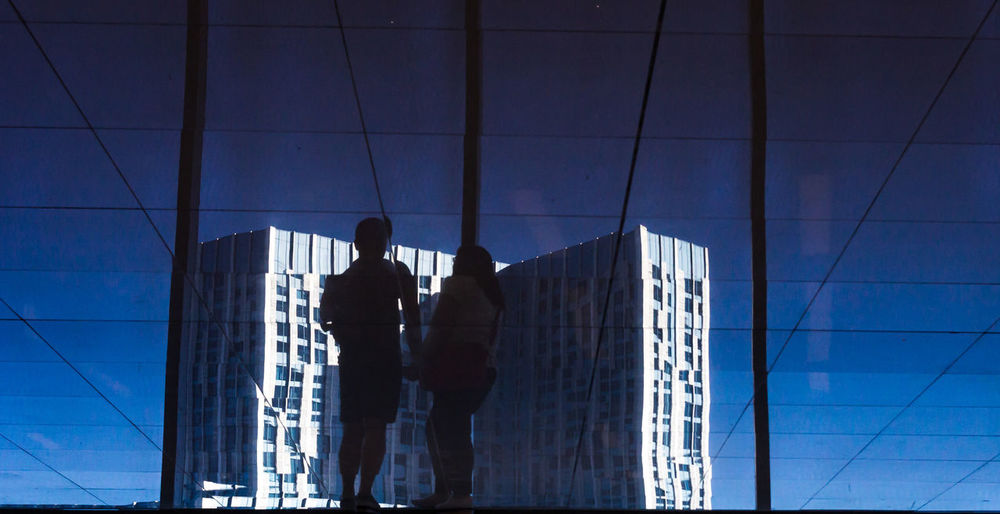 Low angle view of people walking on modern glass building
