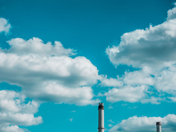 Low angle view of two chimneys against cloudy sky