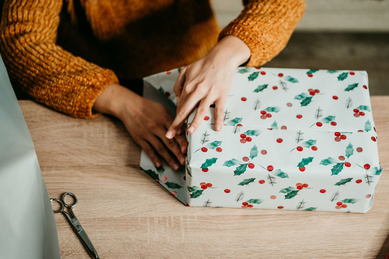 Midsection of woman wrapping christmas gift by table