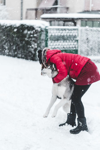 Husky Snow Winter Cold Temperature Day One Person Child Real People Clothing Full Length Women Childhood Motion Snowing Warm Clothing Architecture Leisure Activity Side View Females Nature Outdoors