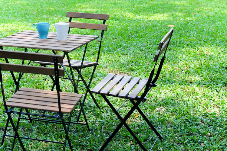 Empty chairs and table on field