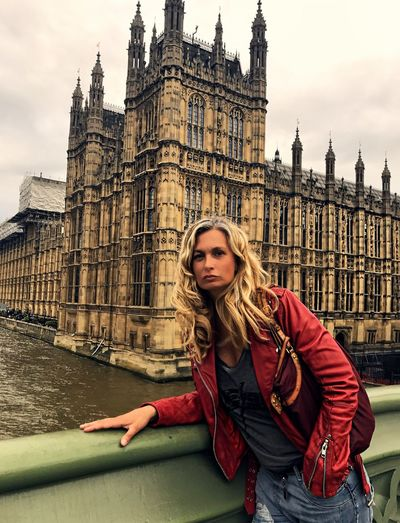 Portrait of young woman wearing leather jacket at westminster bridge in city