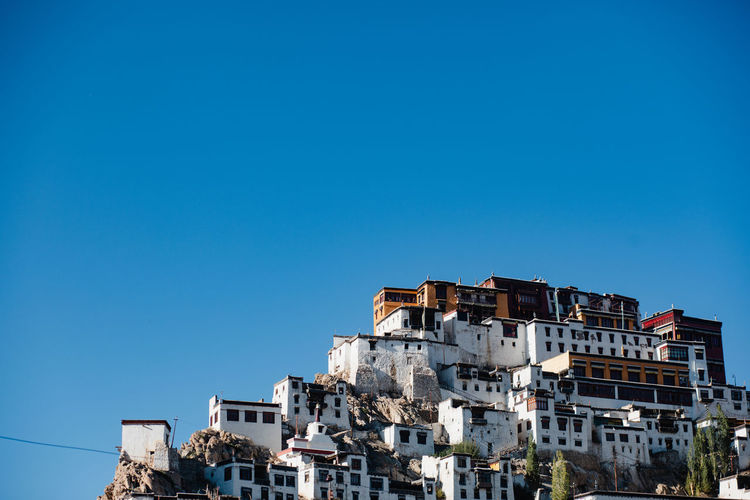 Low angle view of buildings in town against clear blue sky