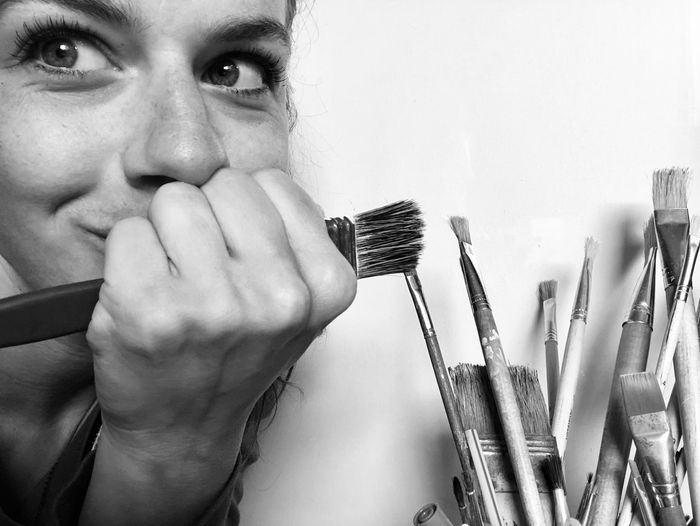 Close-up of woman holding paintbrush while sitting against wall