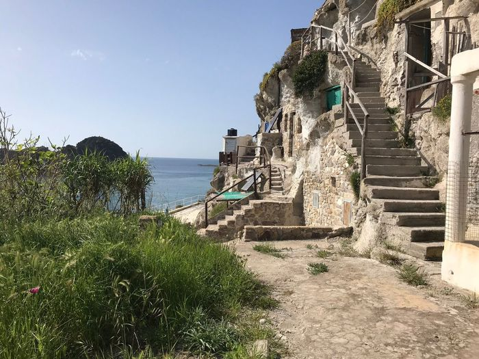 Typical house-caves on wild island Italy Palmarola Building Exterior Sky Water Architecture Sea Built Structure Nature Building Exterior Plant Sunlight Day No People Tree Building Outdoors Beach Land Beauty In Nature Growth Clear Sky
