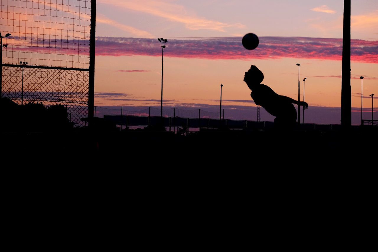 Silhouette man playing with soccer ball against sky during sunset