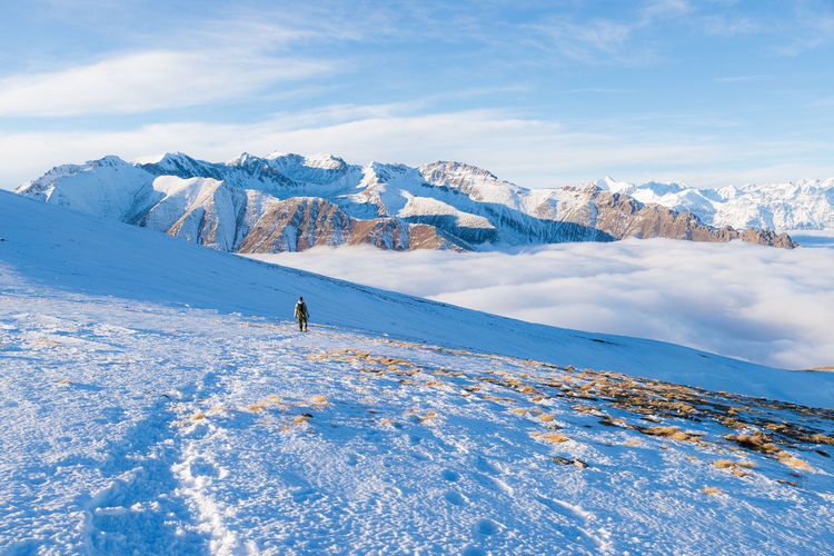 Distant view of woman hiking on snowcapped mountain
