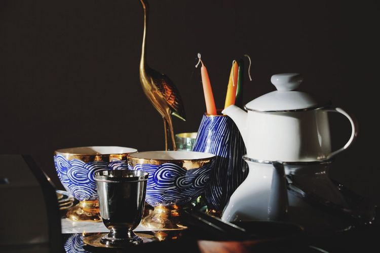 EyeEm Selects Still Life Candle Indoors  Tea Vase No People Design Burning Food And Drink Large Group Of Objects Drink Studio Shot Desk Organizer Close-up Illuminated Black Background Freshness Day Open Edit Pottery Bowls Blue Gold Interior