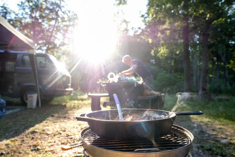 People holding food on barbecue grill against trees