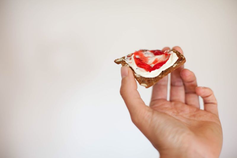 Close-up of hand holding ice cream over white background