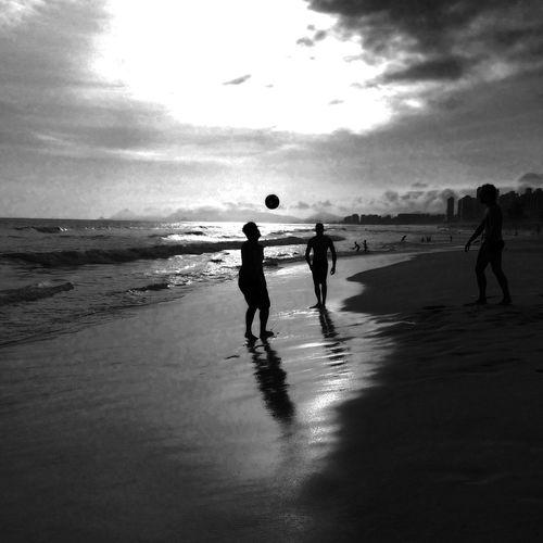 Tourists on beach at sunset
