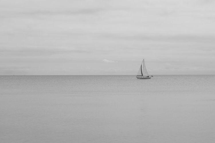 Sailboat sailing on sea against sky
