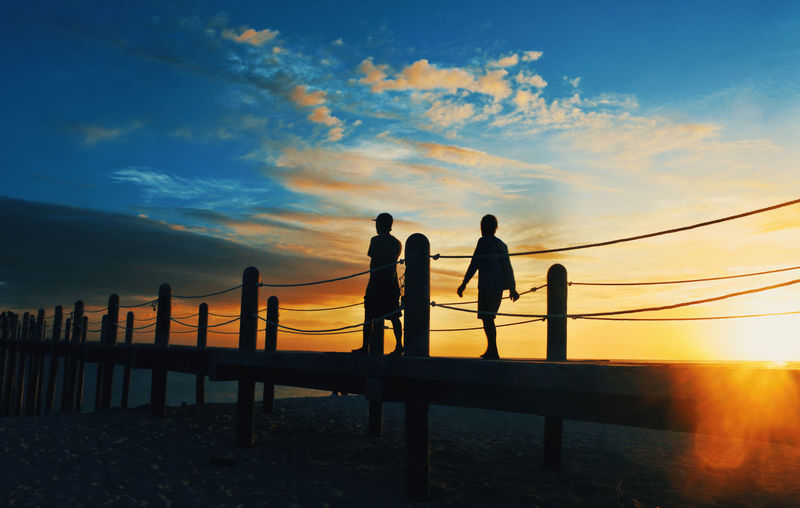 Silhouette people walking on pier at beach against sky during sunset