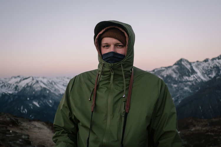 Portrait of young man standing against mountain during winter