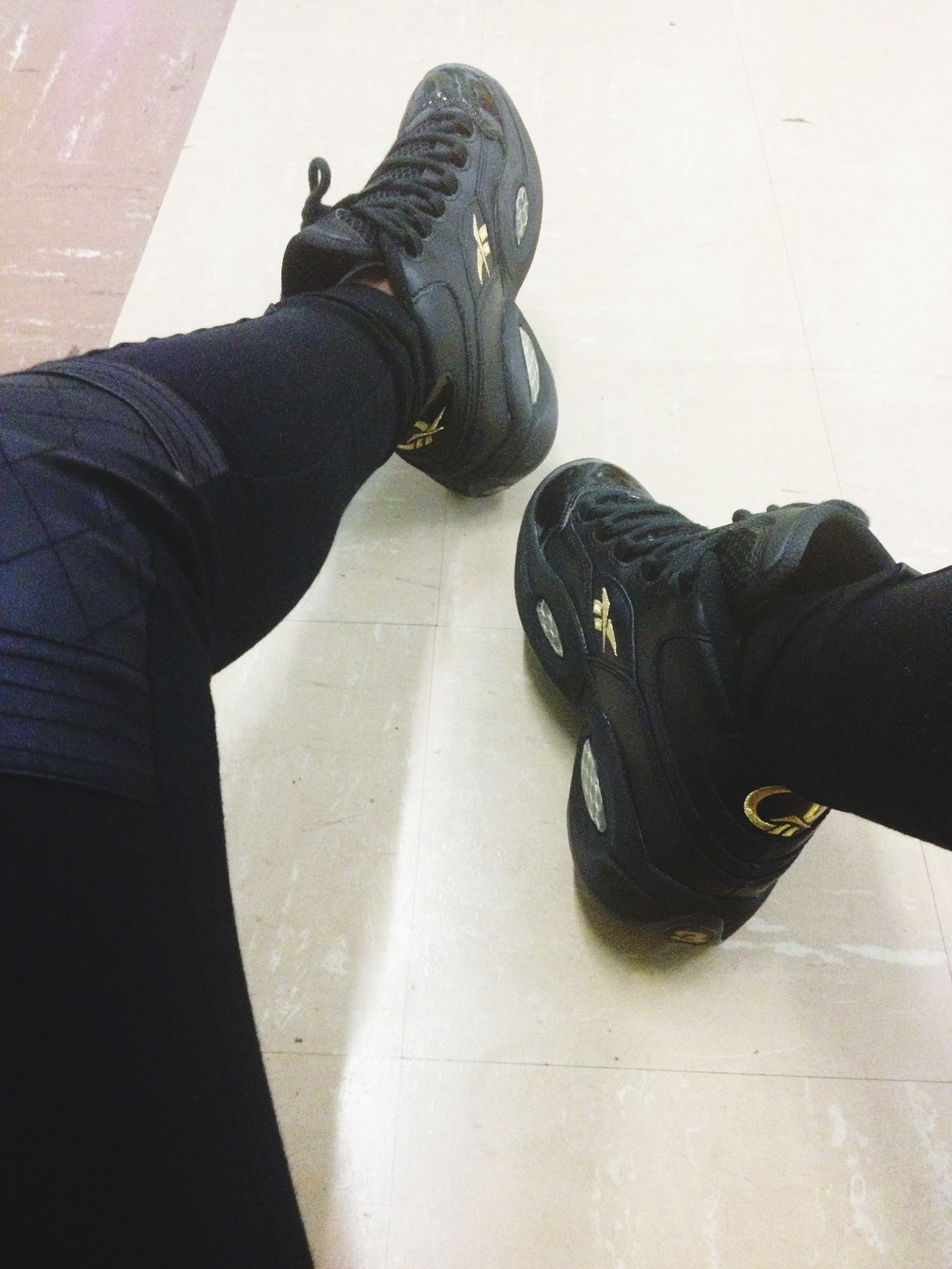 low section, shoe, lifestyles, person, standing, men, casual clothing, leisure activity, indoors, jeans, footwear, wall - building feature, human foot, high angle view, personal perspective, unrecognizable person, day