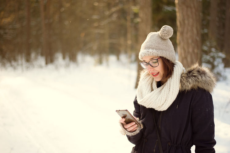 Cold Temperature Communication Day Happiness Holding Knit Hat Leisure Activity Lifestyles Mobile Phone Nature One Person Outdoors Portable Information Device Real People Scarf Smart Phone Smiling Snow Standing Technology Text Messaging Warm Clothing Winter Wireless Technology Young Adult