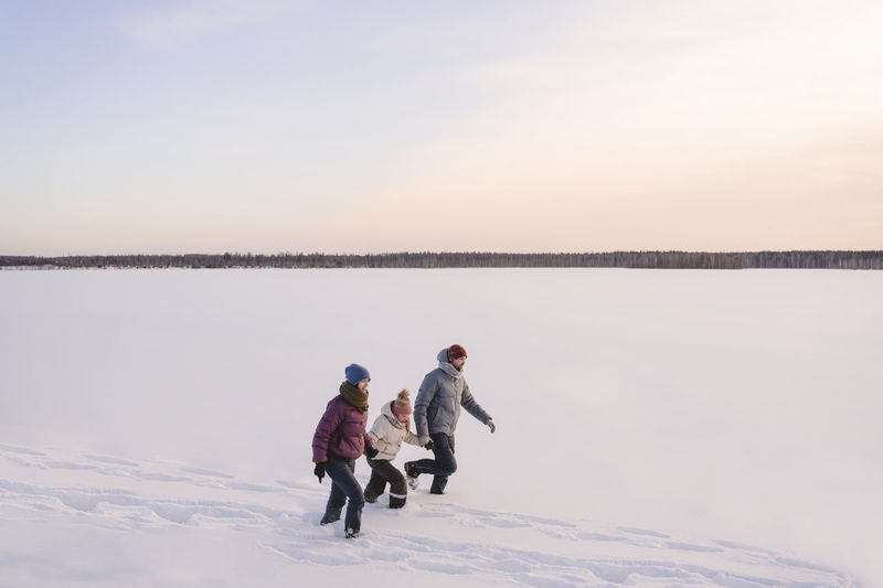 People on lake against sky during winter