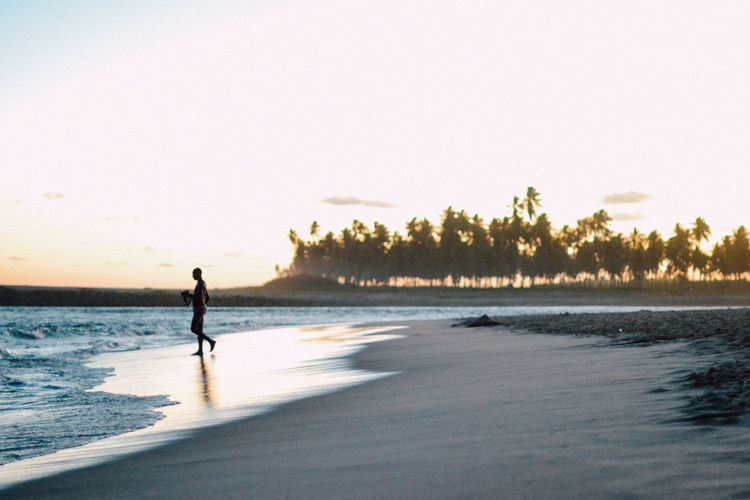 Man walking at beach against clear sky during sunset
