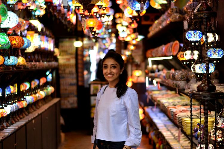 Portrait of smiling woman standing at lighting store