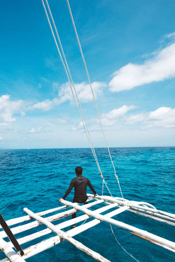 Alone in the sea Water Sea Sky Cloud - Sky Horizon Nautical Vessel One Person Transportation Beauty In Nature Mode Of Transportation Leisure Activity Scenics - Nature Horizon Over Water Real People Nature Day Lifestyles Sitting Non-urban Scene Outdoors Sailboat