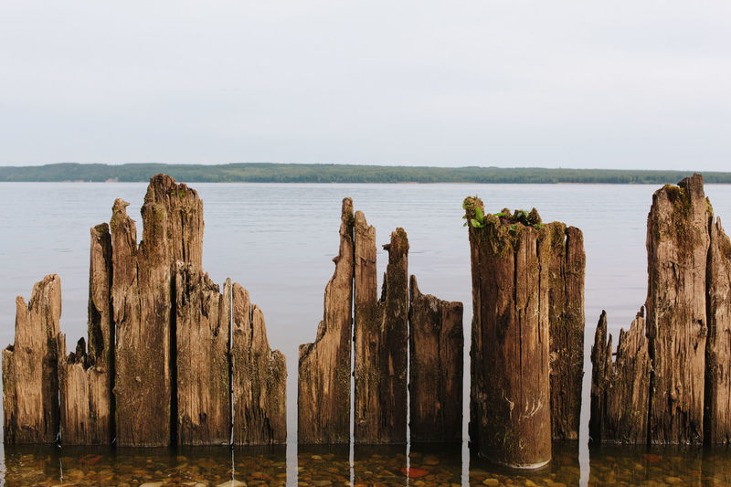 Panoramic view of wooden post on beach against sky
