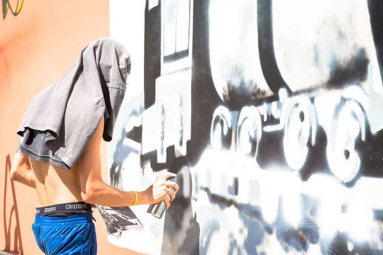 Architecture Art And Craft Built Structure Casual Clothing Day Graffiti Holding Human Body Part Leisure Activity Lifestyles Men Midsection One Person Outdoors Real People Spray Paint Standing Sunlight Wall - Building Feature