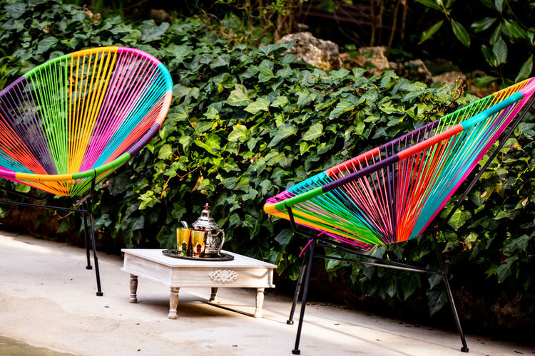 Multi colored chairs on table at yard